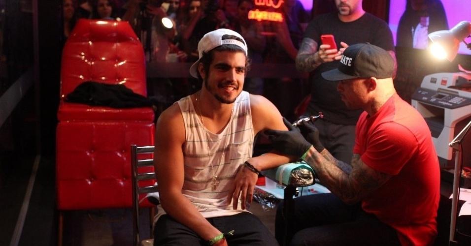 22.set.2013 - Caio Castro faz tatuagem durante o Rock in Rio