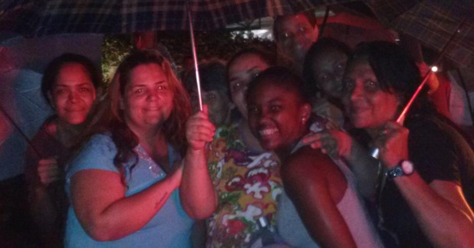 23.set.2013 - Do lado de fora do buffet, fãs do Naldo esperam conseguir entrar no casamento. Debaixo de chuva, elas disseram que caso a ex-mulher do cantor apareça por lá, elas a colocam pra correr