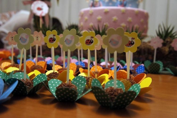 Além de acomodar os brigadeiros em forminhas em formato de flor, a decoradora Taissa Rangel utilizou enfeites com imagens de flores, joaninhas e pássaros para decorar o doce preferido das crianças
