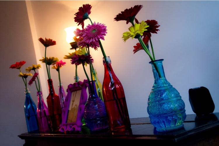 Garrafas de vidro com gérberas deram um colorido especial a outro espaço da festa, nesta decoração de Leticia Alencar