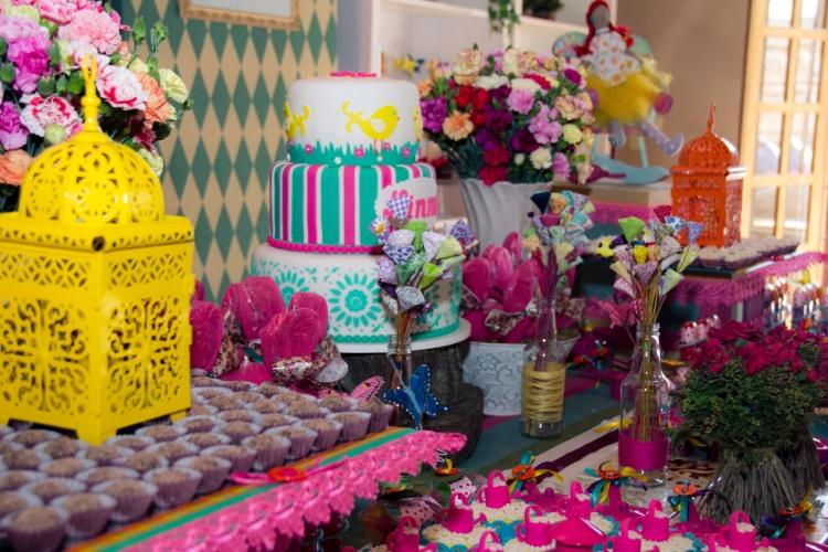Na decoração de Leticia Alencar foram usados cravos de vários tons para compor os arranjos da mesa do bolo. Flores feitas de tecido estampado dispostas em garrafas de vidro conferiram tom lúdico à mesa. Gaiolas de ferro destacaram os doces ao redor
