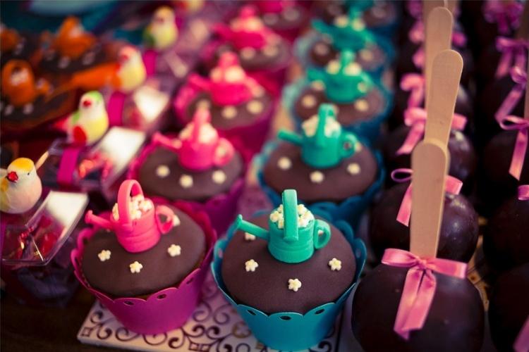 Os cupcakes ganharam regadores feitos com pasta americana. As maçãs do amor foram cobertas com chocolate e decoradas com fita de cetim. Além disso, potinhos de acrílico recheados de bala foram decorados com passarinhos de plástico.  O projeto é de Leticia Alencar