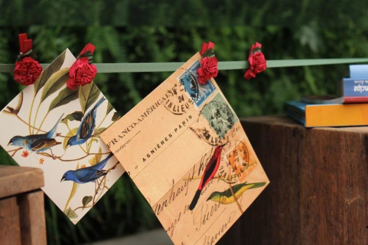 Prendedores de roupa pintados e com flores de tecido foram usados para fixar os papeis de carta estampados no varal decorativo, feito com fita de cetim. A execução é da Decoração do Baile
