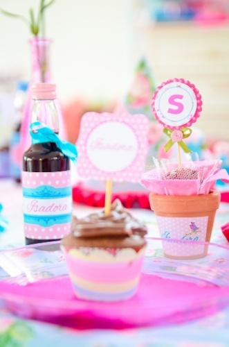 Um vasinho de cerâmica com brigadeiro, uma garrafinha de suco e um cupcake formaram o kit disposto nas mesas para cada convidado desta festa decorada por Gabriela Barreto Piedade