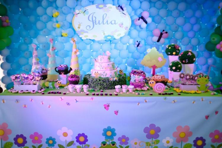 Uma lona estampada com o tema primaveril transformou a mesa de doces num grande jardim, nesta festa de Mirian Macedo. Doces foram espalhados pelo móvel em meio a flores artificiais, sapinhos, centopeias e caracóis de plástico. Ao fundo, um painel de bexigas foi montado para simular um céu com borboletas e abelhas