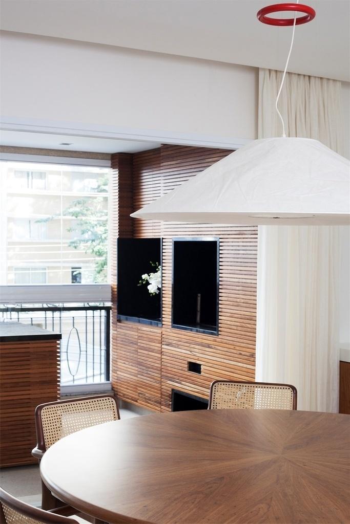 Integrada à sala de jantar, a varanda do apartamento no bairro de Perdizes, em São Paulo, possui churrasqueira, com ilha de apoio. O revestimento que combina filetes de madeira e granito preto dá um ar de sofisticação à área de lazer. As arquitetas Débora Stefanelli e Pérola Machado assinam o projeto de reforma e interiores da residência