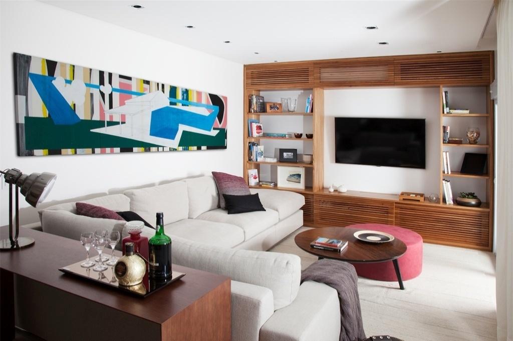 Para aproveitar melhor a metragem do espaço e transformar a sala de estar em home theater, as arquitetas Débora Stefanelli e Pérola Machado optaram pelo mobiliário sob medida: o sofá em