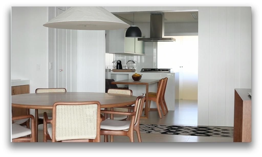 Para integrar a copa-cozinha com a sala de jantar e ao mesmo tempo garantir privacidade aos moradores, as arquitetas Débora Stefanelli e Pérola Machado optaram por uma estrutura divisória de madeira, com portas de correr e acabamento em laca branca fosca, chamado de painel