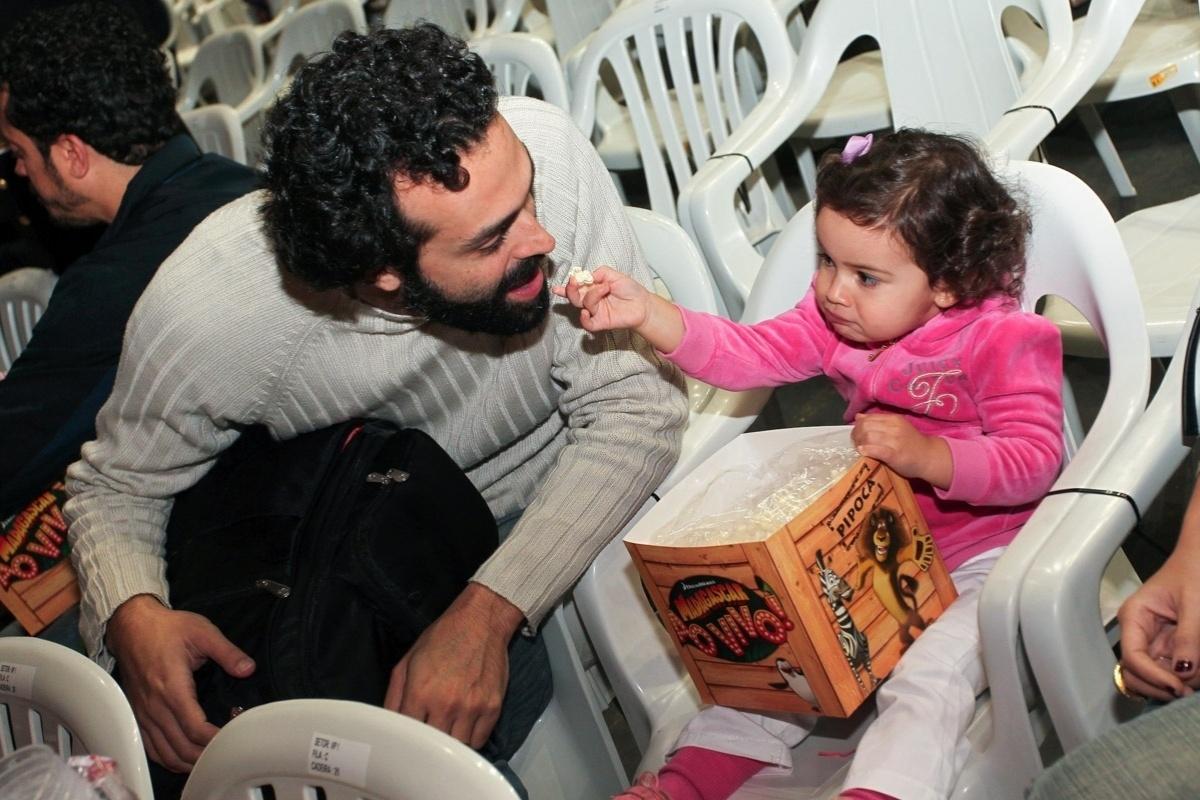 28.set.2013 - Laura, filha de Mariana Belém com Christiano Saab, dá pipoca na boca do pai durante o musical