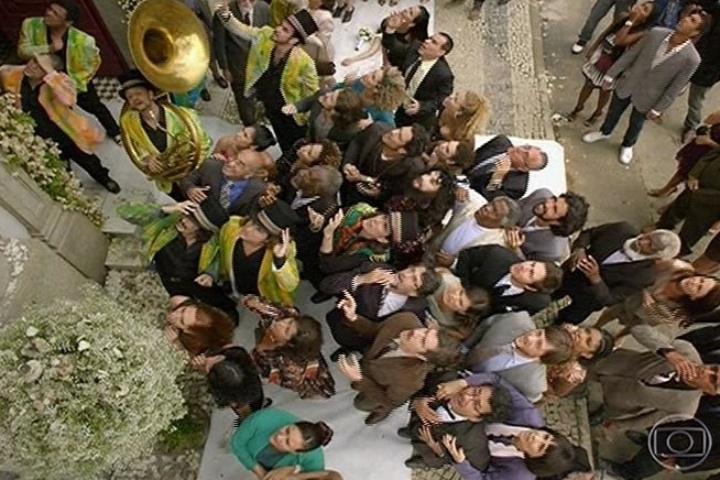 A população de Saramandaia observa João Gibão (Sérgio Guizé) no topo da igreja