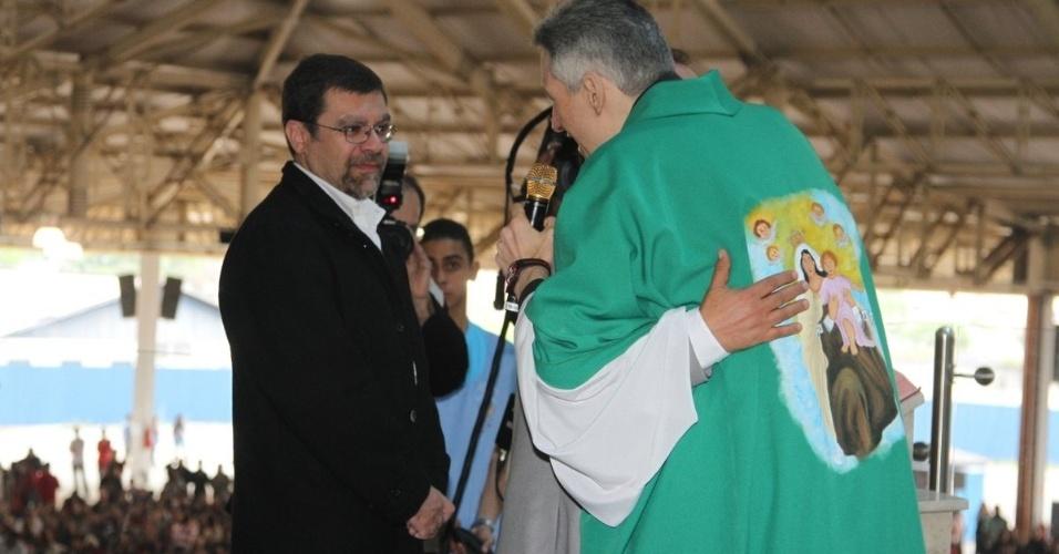 29.set.2013 - 29.set.2013 - Claudio Pessuti, sobrinho de Hebe Camargo, recebe abraço do Padre Marcelo Rossi