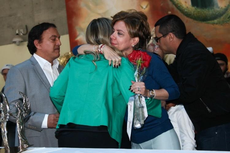 29.set.2013 - Astrid Fontenelle abraça Helena, mulher de Claudio (sobrinho de Hebe), na missa que marcou um ano da morte da apresentadora