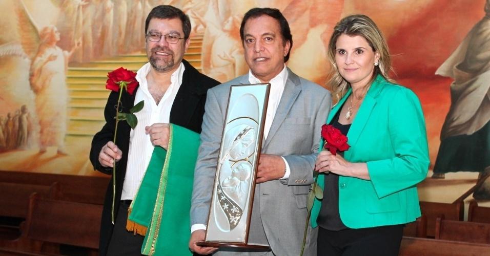 29.set.2013 - Familiares de Hebe Camargo seguram imagem de Nossa Senhora após missa que marcou um ano da morte da apresentadora