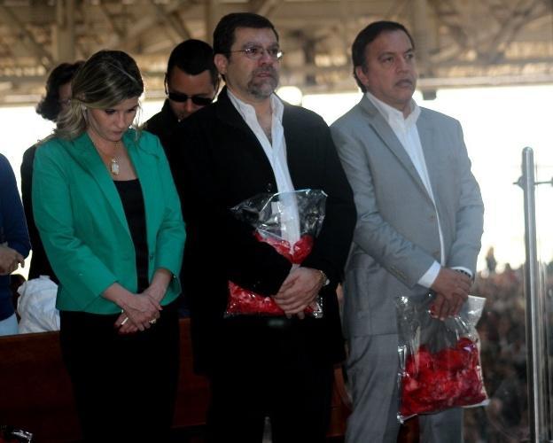 29.set.2013 - Filho e sobrinho de Hebe Camargo seguram saco com pétalas de rosas na missa que marca um ano da morte da apresentadora