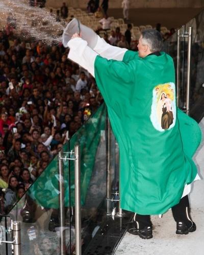 29.set.2013 - Padre Marcelo joga água benta nos fiéis ao fim da missa