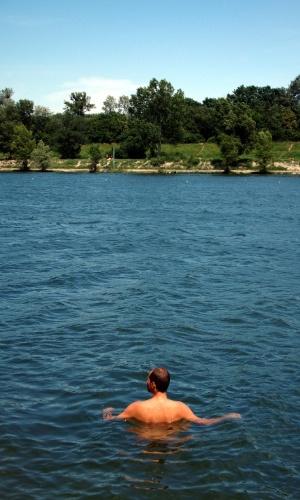 Banhista nada no rio Danúbio, em Viena. Com mais de nove mil hectares de área, o parque nacional Donau Auen abriga praias onde é possível praticar naturismo em ambientes voltados, exclusivamente, para o público gay masculino como o setor Toter Grund (na foto)