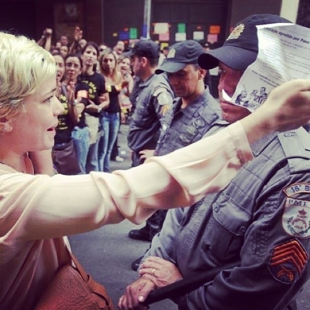 """1.out.2013 - Leandra Leal participou nesta terça da manifestação em prol aos professores do ensino público que aconteceu na Cinelândia, no centro do Rio. """"Educação e Cultura lado a lado! Força professores"""", escreveu a atriz na legenda da foto. No registro, Leandra aparece enfrentando um policial  militar"""