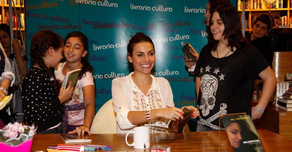 """2.out.2013 - Mel Fronckowiak assina obras de seus fãs no lançamento de seu livro """"Inclassificável: Memórias de estrada"""" em livraria de São Paulo. A atriz e cantora, famosa por sua participação na novela """"Rebelde"""", é atual namorada do ator Rodrigo Santoro"""