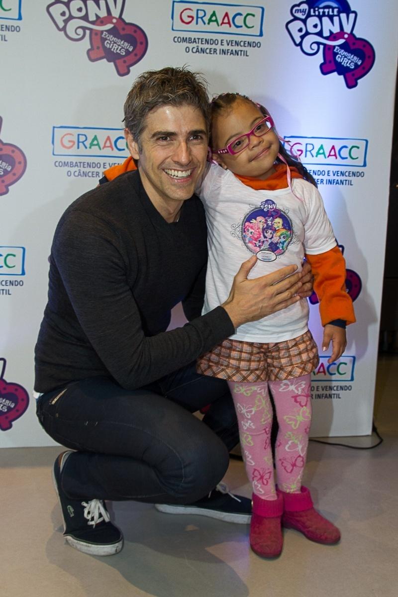 3.out.2013 - O ator Reynaldo Gianecchini posa ao lado de criança atendida pelo GRAACC no lançamento do filme