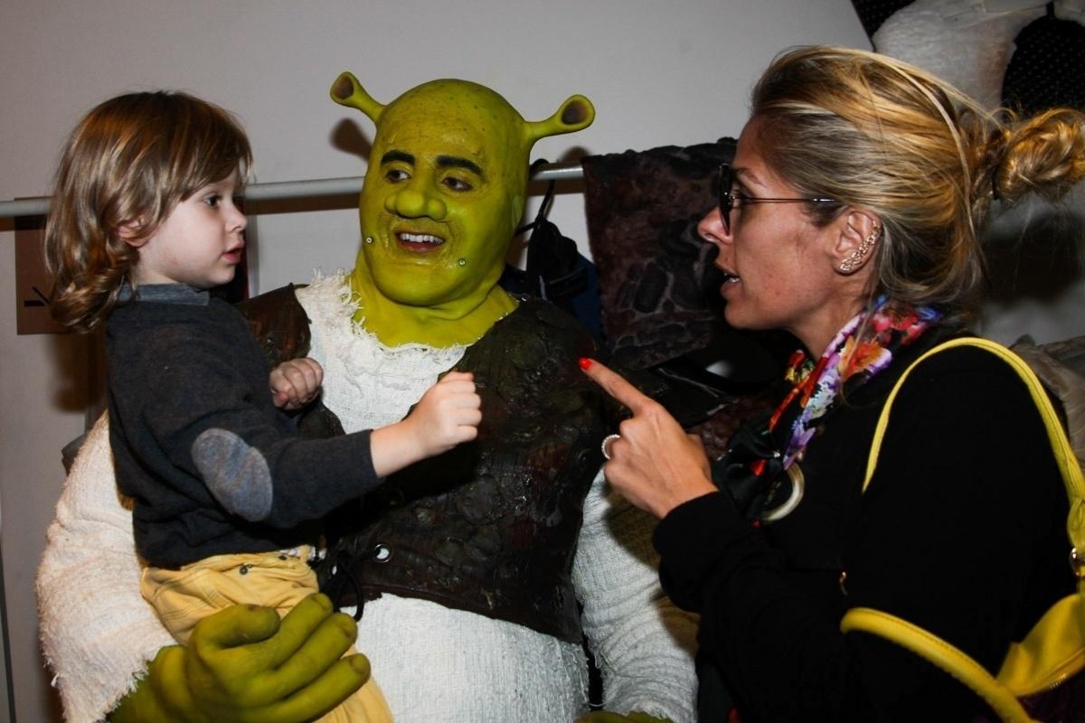 6.out.2013 - A apresentadora Adriane Galisteu apresenta o personagem Shrek ao filho Vittorio nos camarins do espetáculo em São Paulo