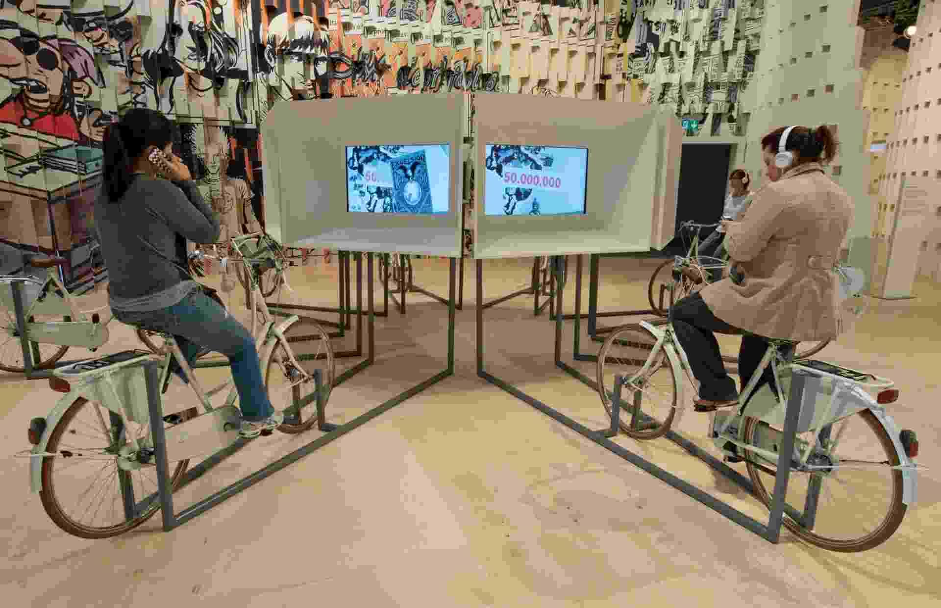8.out.2013 - Pessoas usam bicicletas como gerador de energia para assistir vídeos sobre literatura brasileira na Feira Literária de Frankfurt 2013, na Alemanha - AFP PHOTO / DPA / BORIS ROESSLER