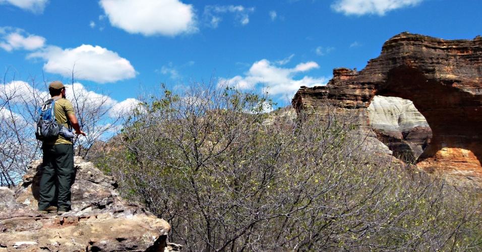 Viajantes escalam mirante que oferece visão da Pedra Furada, no Parque Nacional Serra da Capivara, Piauí