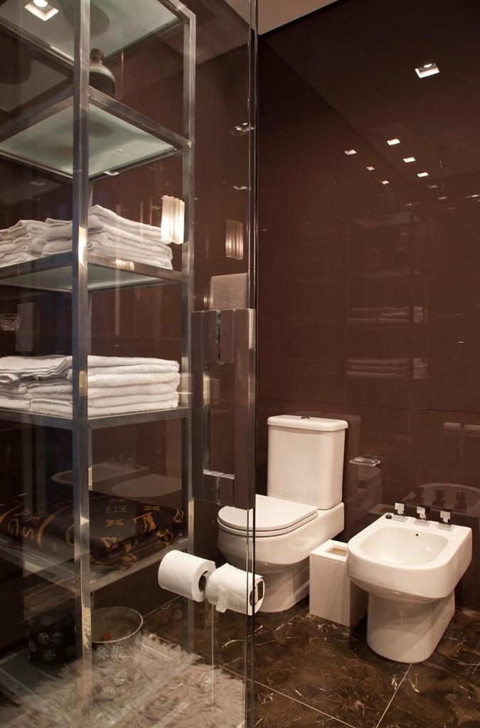 O marrom foi a cor eleita para o banheiro da suíte do morador. No ambiente, as paredes são revestidas por vidro e o piso é de mármore marrom Imperial, da Marmogrini. As louças são da Deca e os metais, Interbagno. Destaque para a prática estante em aço e vidro para guardar a roupa de banho. A reforma do apartamento com vista para a Paulista foi projetada pelo designer de interiores Oscar Mikail