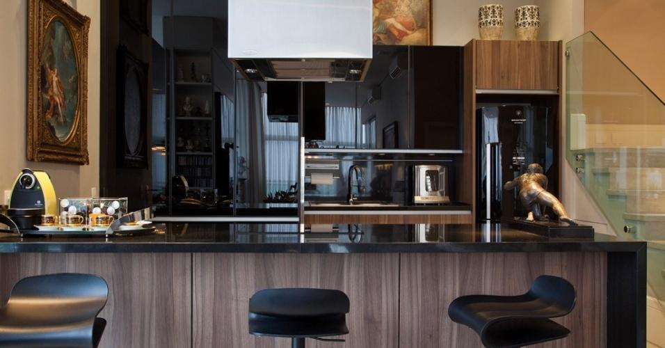 Totalmente integrada ao living, a cozinha - da Kitchens - possui bancada com tampo de mármore preto absoluto e base revestida por laminado imitando madeira. Os armário e nichos em madeira e vidro preto embutem os eletrodomésticos e dão um ar sóbrio ao espaço. As banquetas altas são da Montenapoleone e a coifa é da Pulsar. O projeto de reforma e interiores é do designer de interiores Oscar Mikail