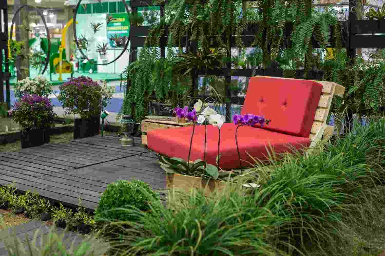 """Para o ambiente """"Cantinho Renovo"""", o paisagista Rodrigo Jensen optou por materiais de reuso e peças antigas em 90% da montagem. Os conhecidos paletes se transformaram em um jardim vertical, em piso e também usados para confeccionar a estrutura do móvel """"almofadão"""". Caixotes viraram um vaso para orquídeas e uma mesa lateral. A mostra de paisagismo integra a 16ª Fiaflora ExpoGarden, no Centro de Exposições Imigrantes, em São Paulo - Haroldo Saboia/ UOL"""