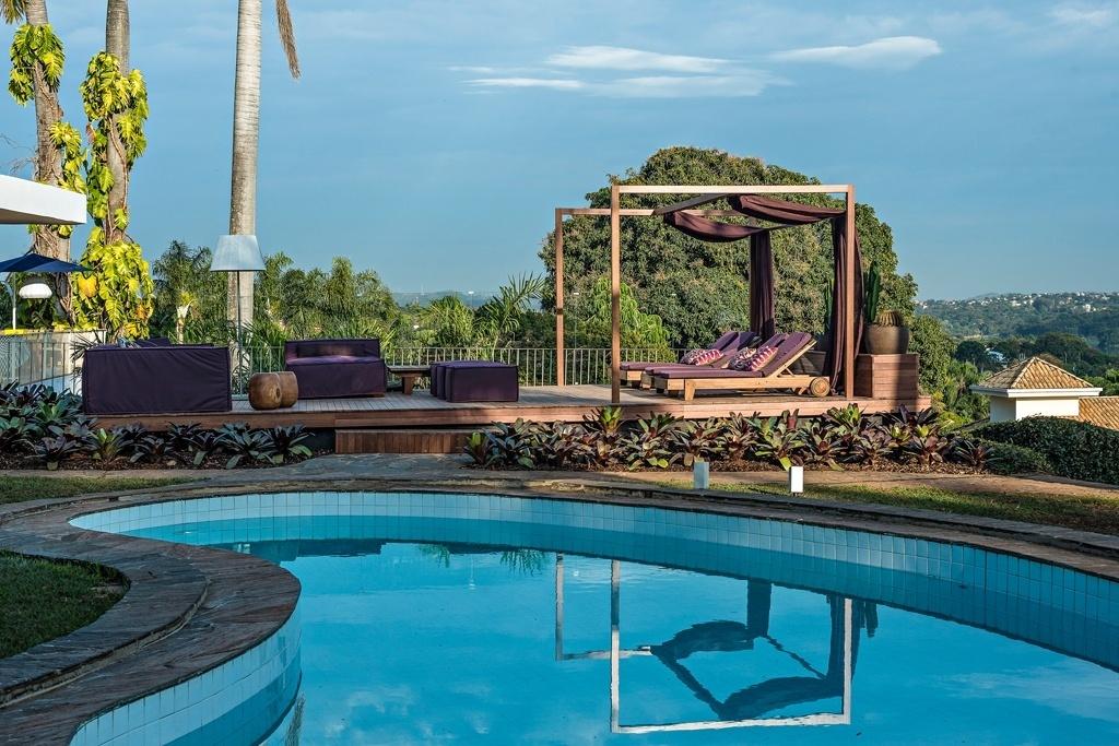 Casa Cor MG - 2013: A arquiteta Anaíne Vieira Pitchon assina o Jardim da Piscina, onde o paisagismo conta com bromélias e cactáceas. O destaque da decoração, porém, fica com dois elementos: a cor púrpura usada nos tecidos e o dossel que envolve as espreguiçadeiras