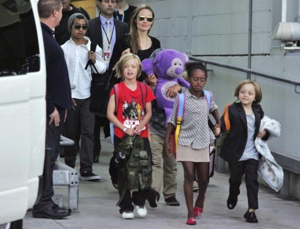 Angelina Jolie com os filhos (da esquerda para a direita): Maddox (de gorro), Shiloh (de camiseta vermelha), Zahara e Knox, em um aeroporto de Sidney, na Austrália