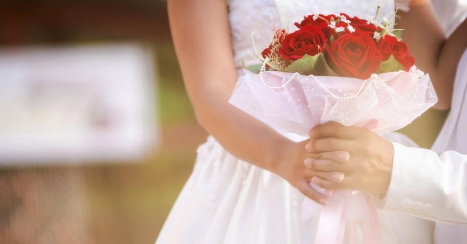 A força das rosas vermelhas é equilibrada com a delicadeza das pérolas na borda do buquê e do tecido que dá sustentação a ele