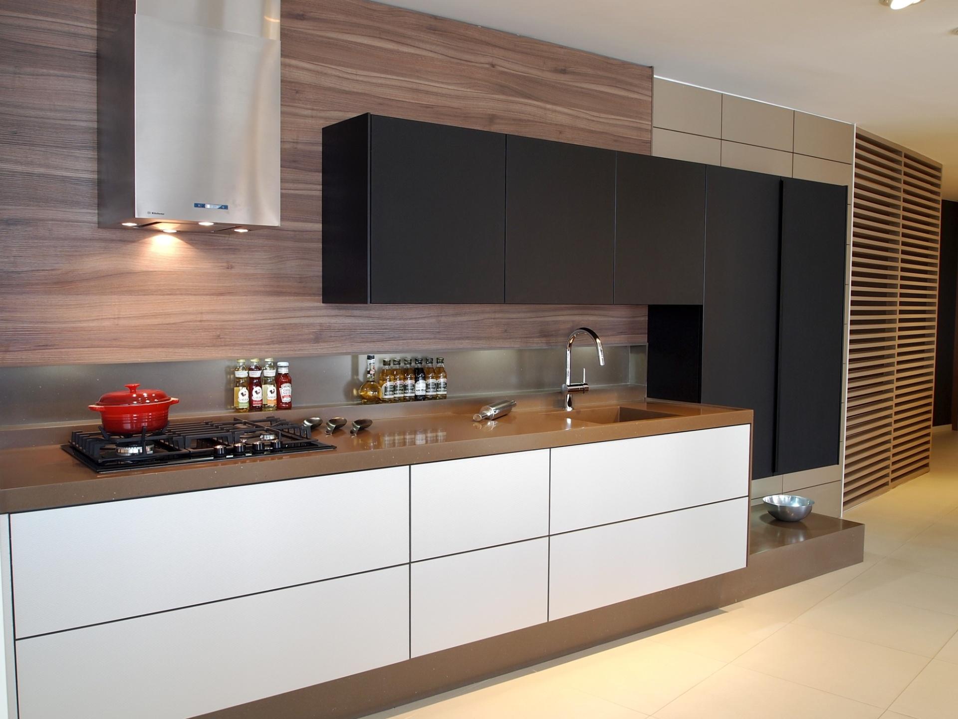 Adaptável a pequenos espaços, o projeto da Kitchens (www.kitchens.com.br) une a área de armazenamento à pia e ao cooktop. As gavetas, sem puxadores, são revestidas em alumínio Silver Cotele com sistema de abertura elétrico por meio de toque. Os armários superiores são em vidro preto fosco e o tampo em Corian Suede