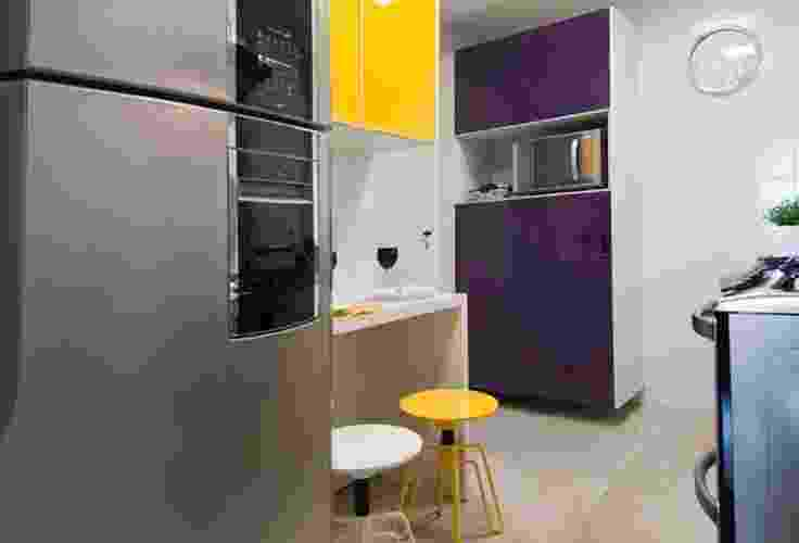 Na cozinha planejada da Linea Mobili (www.lineamobili.com.br), as portas dos armários ganharam cores vibrantes, aplicadas na madeira com a técnica da pintura automotiva. O móvel conta com estreita mesa com duas banquetas para refeições rápidas - Divulgação