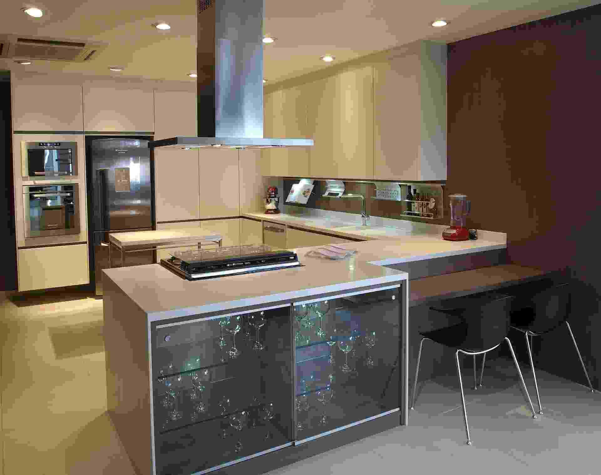 Outro projeto de cozinha planejada da Kitchens (www.kitchens.com.br) aproveita todo o espaço para compor um uma grande área de armazenamento, na qual os armários são feitos de laminado branco Cotele. Em frente à bancada, o diferencial são as portas deslizantes e prateleiras de vidro ao lado de uma mesa integrada ao tampo - Divulgação