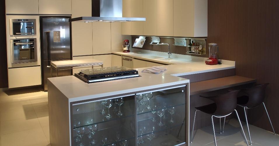 Outro projeto de cozinha planejada da Kitchens (www.kitchens.com.br) aproveita todo o espaço para compor um uma grande área de armazenamento, na qual os armários são feitos de laminado branco Cotele. Em frente à bancada, o diferencial são as portas deslizantes e prateleiras de vidro ao lado de uma mesa integrada ao tampo