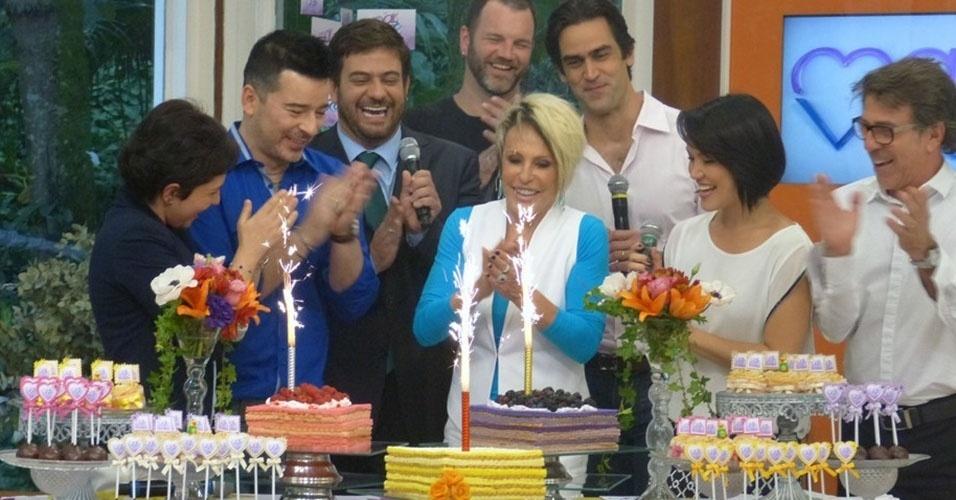 """18.out.2013 - No dia do aniversário de 14 anos do """"Mais Você"""", Ana Maria Braga e repórteres cantam """"Parabéns"""" em frente a mesa de doces com três bolos"""
