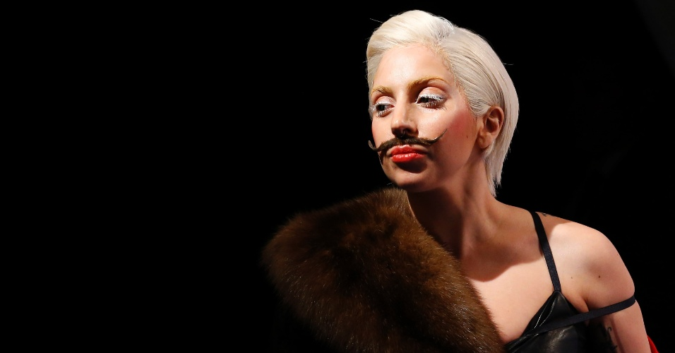 24.out.2013 - Com os cabelos curtos e loiros, de lingerie e bigode postiço, a cantora Lady Gaga promoveu seu novo álbum,