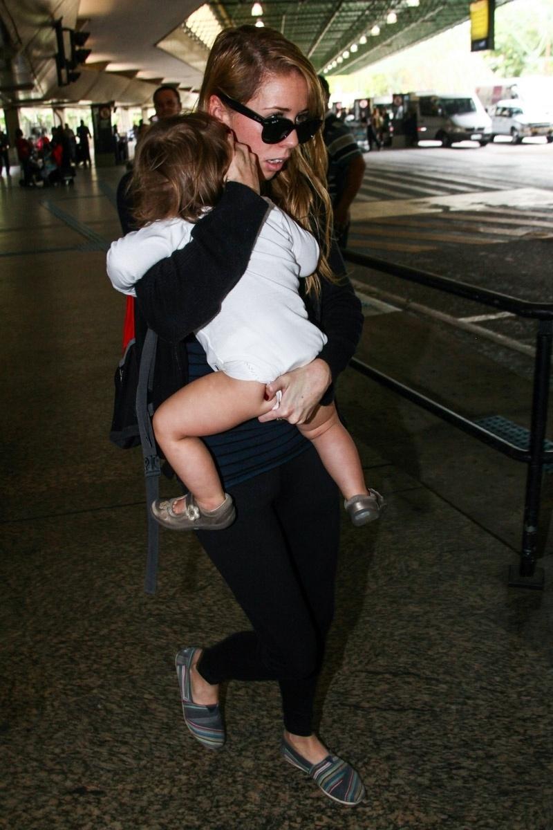 25.out.2013 - Mulher tenta esconder o rosto de Luna, filha da atriz Uma Thurman, que desembarcou com a menina no aeroporto de Guarulhos, em São Paulo