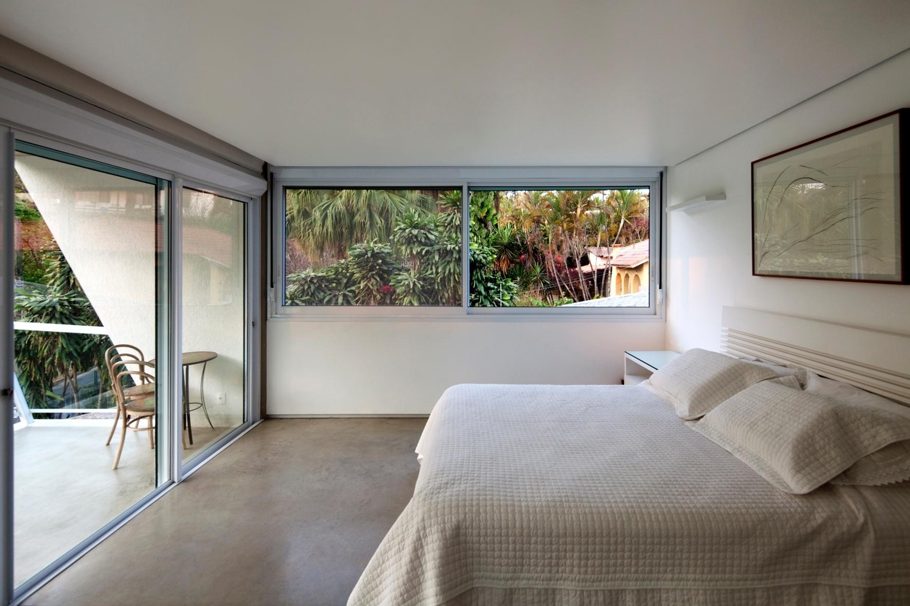 Ampla e agraciada com intensa luminosidade natural, a suíte do casal possui terraço voltado para a Lagoa da Pampulha e janelão com vista para a vegetação dos arredores. O piso em cimento contrasta com o ambiente monocromático e