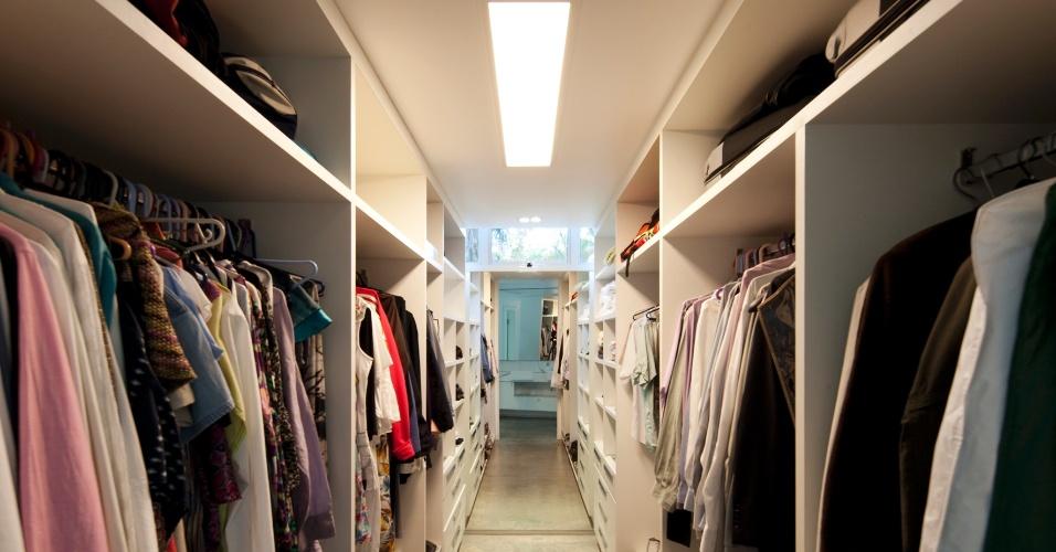 O generoso closet da suíte do casal possui armários distribuídos em toda a extensão das paredes paralelas, além de prático espelho que reflete o banheiro dos proprietários. A Casa FP, em BH, foi projetada pelo arquiteto João Diniz