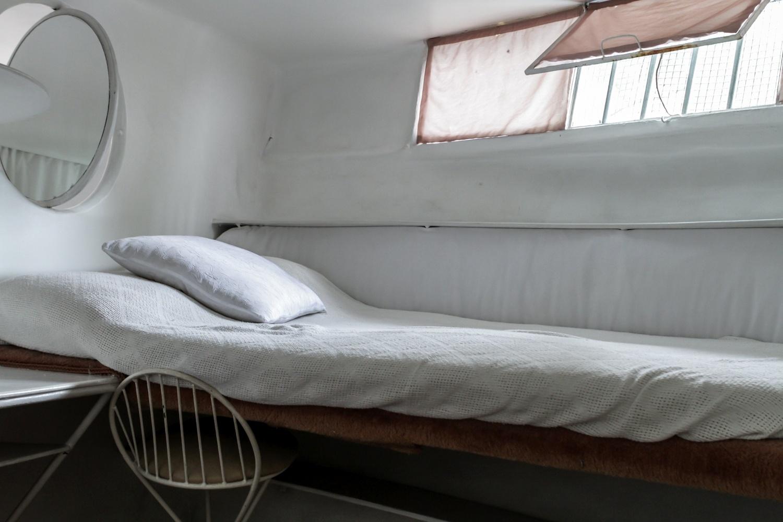 Na imagem, um dos quartos de solteiro/ hóspedes da Casa Bola, assinada por Eduardo Longo. Assim como grande parte do mobiliário, a cama e as prateleiras do cômodo são integradas ao corpo construtivo da residência