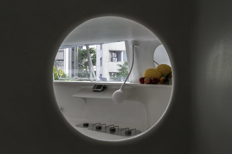 Da abertura circular é possível avistar a cozinha da Casa Bola, que foi construída em 1970 e tem projeto do arquiteto Eduardo Longo. Os móveis monocromáticos possuem cantos arredondados. Tais características não são despropositadas, elas servem para criar uma percepção mai