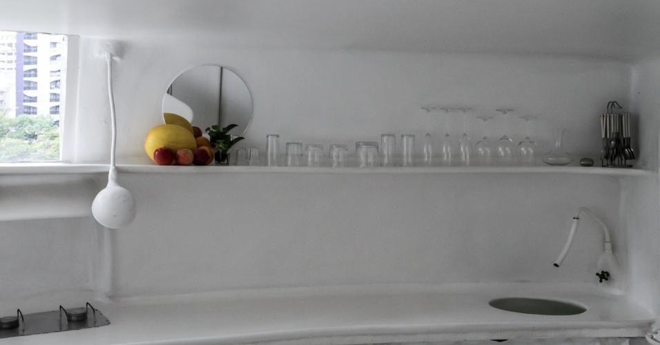 Na cozinha, uma prateleira acomoda os copos e outros utensílios, além de um espelho e uma fruteira - de onde provém o ponto de cor concentrada no ambiente. Com cantos arredondados, a bancada se estende da pia (à dir.), ao cooktop. Para a melhor iluminação da área de preparo dos alimentos, uma luminária que lembra as iluminações públicas. A Casa Bola tem projeto do arquiteto Eduardo Longo