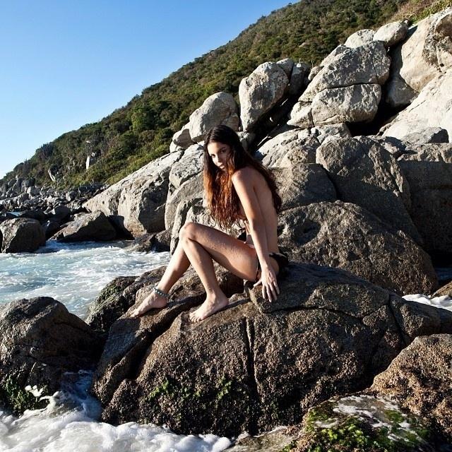 30.out.2013 - O fotógrafo André Nicolau divulgou uma imagem do ensaio feito por Stephany Brito. Na foto, a atriz aparece de topless sentada em um pedra