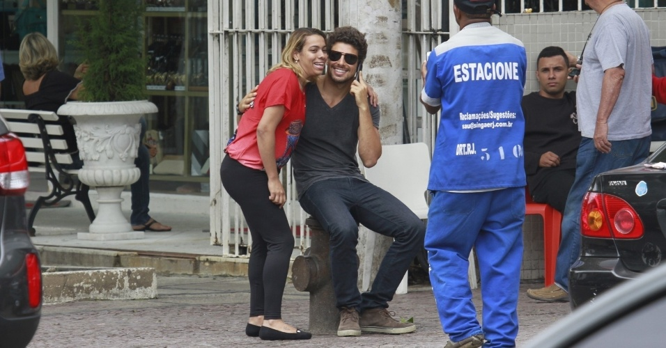 1.nov.2012 - Falando ao telefone, Cauã Reymond tira foto com fã em rua da Barra, zona oeste do Rio. O ator é alvo de recentes boatos que apontam que ele teria traído Grazi com a atriz Isis Valverde, o que teria provocado o fim do casamento