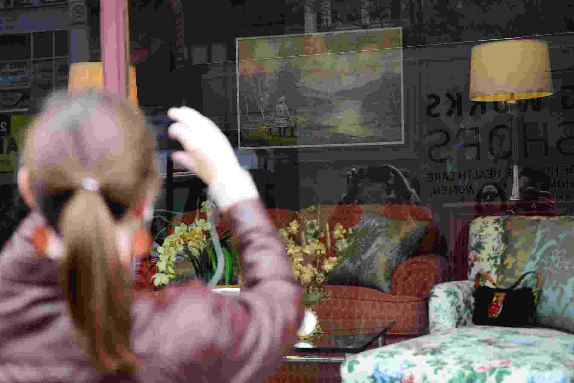 """30.out.2013 - Mulher fotografa obra """"vandalizada"""" por Banksy. O grafiteiro a comprou por US$ 50 dólares e a devolveu com uma imagem extra: um nazista sentado junto à paisagem - AFP"""
