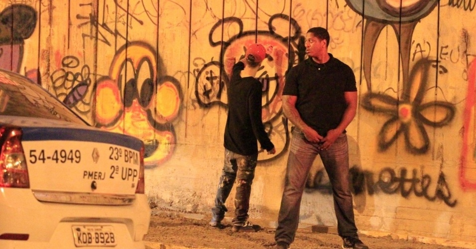 5.nov.2013 - Escoltado por segurança, Justin Bieber grafita muro do bairro de São Conrado, no Rio de Janeiro, durante a madrugada. O cantor e sua equipe foram para o local por volta das 3h. De acordo com a agência de fotografias AgNews, os fotógrafos presentes no local foram agredidos pelos seguranças de Bieber e a polícia chegou a ser chamada. O astro teen ficou grafitando por cerca de três horas e atendeu a fãs