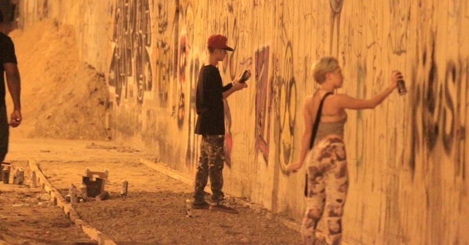 5.nov.2013 - Justin Bieber grafita muro do bairro de São Conrado, no Rio de Janeiro, durante a madrugada. O cantor e sua equipe foram para o local por volta das 3h. De acordo com a agência de fotografias AgNews, os fotógrafos presentes no local foram agredidos pelos seguranças de Bieber e a polícia chegou a ser chamada. O astro teen ficou grafitando por cerca de três horas e atendeu a fãs