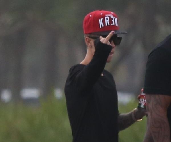 5.nov.2013 - Justin Bieber mostra o dedo do meio para paparazzi ao ver que está sendo fotografado andando na orla da praia da Barra da Tijuca